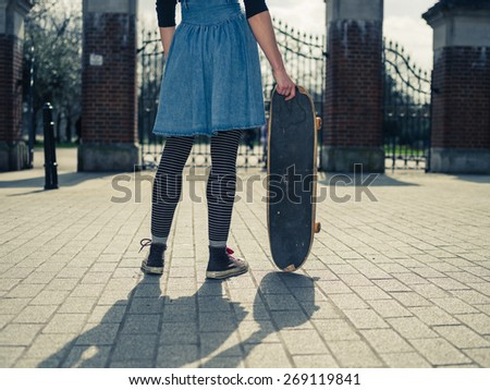 A young woman is standing outside a park by the gates and is holding a skateboard
