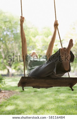 A young woman is swinging on a swing in a park setting.  Vertical shot.