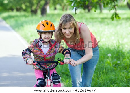 A young woman is teaching girl to ride bicycle in summer park #432614677