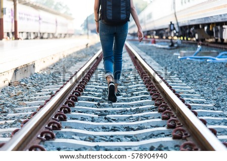A young woman is walking on the railroad tracks #578904940