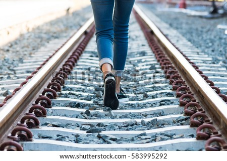 A young woman is walking on the railroad tracks #583995292