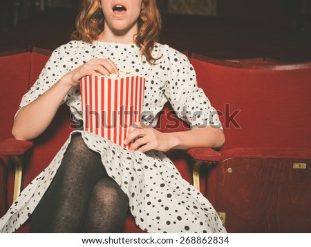 A young woman is watching an exciting  movie and is eating popcorn at the cinema