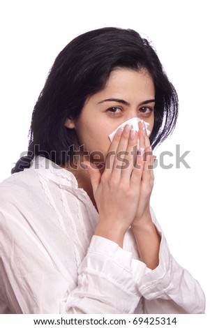 A young woman isolated whiping her nose after caching the flu - stock photo