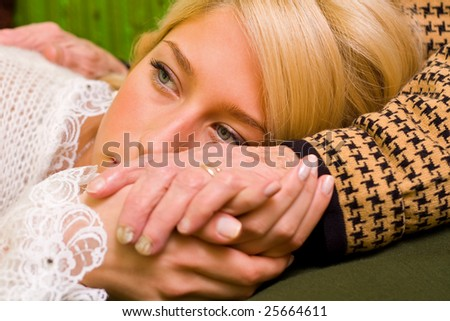 A young woman  laying her head on her grandmother's legs - part of a series.