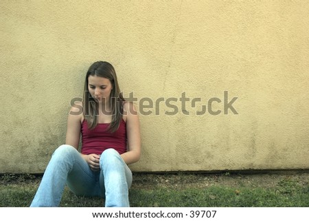A young woman leaning against a wall.