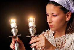 A young woman Lighting the candles for Jewish Sabbath, isolated on black