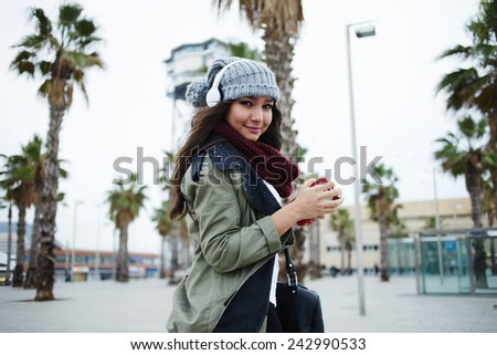 A young woman listening to music on her headphones walking outdoors