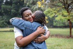 A young woman living with HIV embracing her friend at a park in Nairobi, Kenya