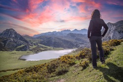 A young woman looking at the beautiful Covadonga lake in Asturias in a beautiful spring sunset, Picos de Europa. Spain