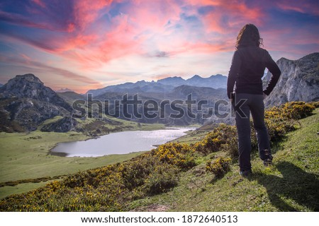 A young woman looking at the beautiful Covadonga lake in Asturias in a beautiful spring sunset, Picos de Europa. Spain Stockfoto ©
