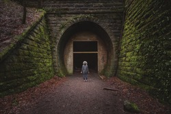 A young woman looks ahead into a dark, empty void that is the Neidpath Train Tunnel at Peebles, Scottish Borders, Scotland.