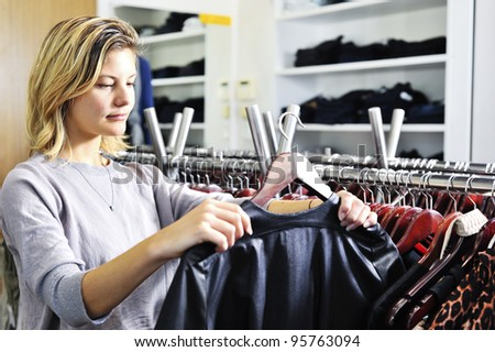 "a young woman looks at a jacket in a clothing store; this model has a very natural ""normal"" look."