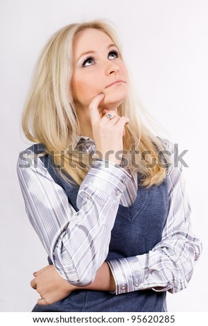 A young woman looks up in thought.