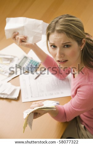 A young woman looks upset while sorting through her old receipts.  Vertical shot.