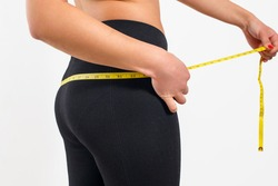 A young woman measures the volume of her pelvis with a centimeter tape. On a white background.