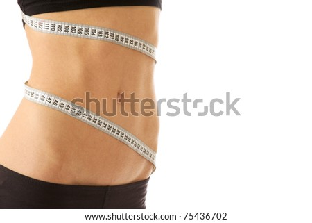 A young woman measuring her waist