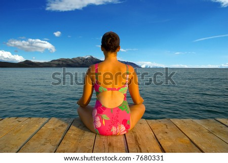 A young woman meditating and relaxing during evening hours in an amazing scenery