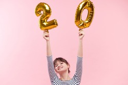 A young woman of Asian nationality is holding in her hands inflatable balloons in the form of numbers 20 twenty percent. The concept of discounts, sales and cashback. Pink studio background