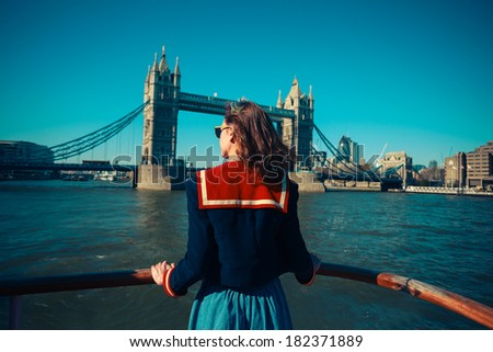 A young woman on a boat is looking at Tower bridge and the London skyline