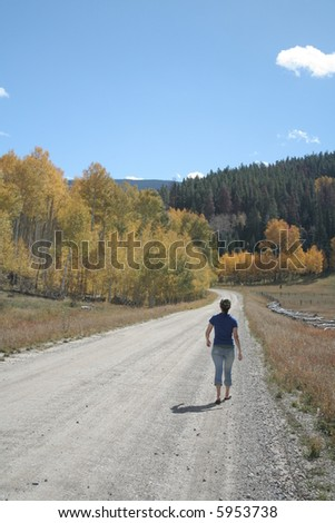 A young woman on a dirt road during yellow, autumn leaves
