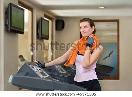 A Young Woman On A Treadmill At The Gym, Wiping Sweat Off ...