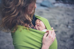 A young woman on the beach with her baby in a sling