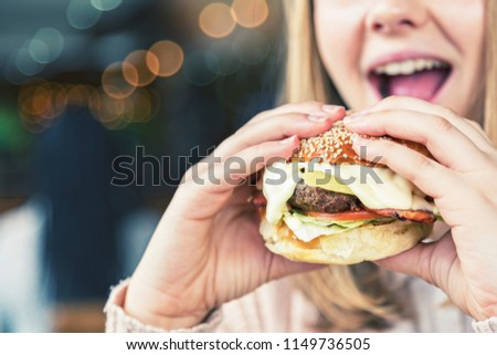 A young woman opens her mouth about to eat a huge cheeseburger crammed with fillings.