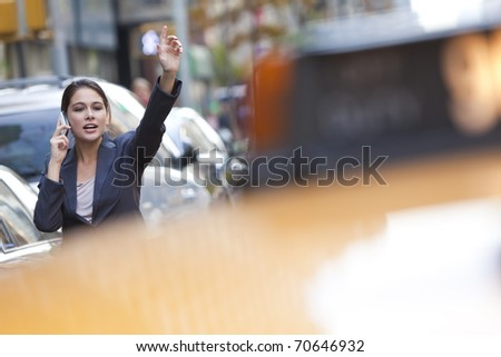 A young woman or businesswoman hailing a yellow taxi cab while talking on her cell phone in a modern city