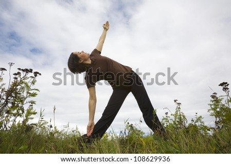 A young woman outdoors exercising doing yoga stretches.