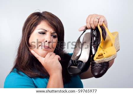 A young woman over a silver background trying to decide on which pair of shoes she should wear.