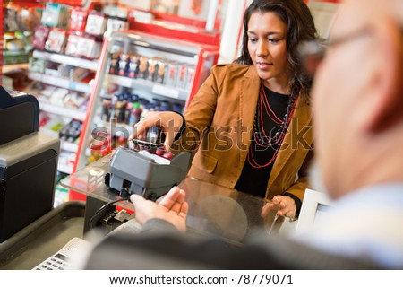 A young woman paying for grocery purchase with a mobile phone