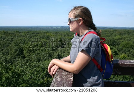 A young woman peering over a ledge at the view. Horizontally framed shot.