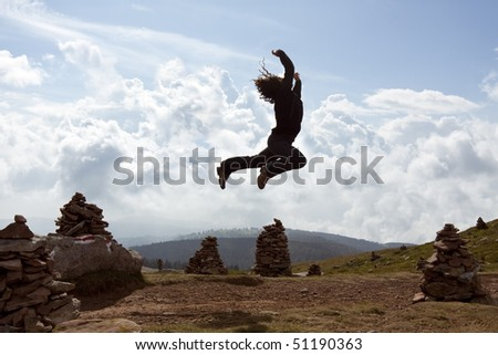 A young woman performs a jumping scene in front of a cloudy sky in the mountains above some mystic&old stony sculptures