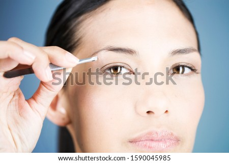 A young woman plucking her eyebrows