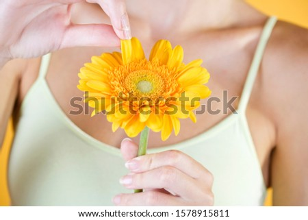 A Young Woman Plucking The Petals From An Orange Flower