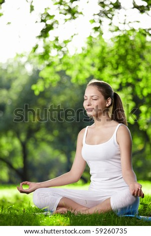 A young woman practices yoga in the park