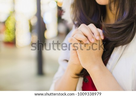 A young woman praying for God's blessings with the power and power of the sacred, giving herself luck and showing her forgiveness with the power of religion, faith, worship, Christian concept.