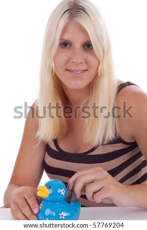 A young woman puts a coin in a piggy bank