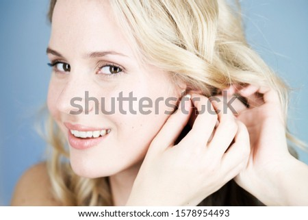 A young woman putting on earrings