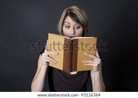 A young woman reaches a surprising part of a story she's reading in a book.