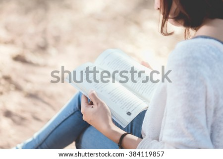 A young woman reading a book. Book in woman hands. Woman reading a book in park.