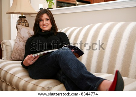 A young woman reads a magazine while sitting on her couch
