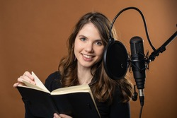 A young woman reads for a podcast as a voice actor