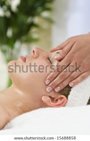 A young woman relaxing at a health spa while having a facial treatment