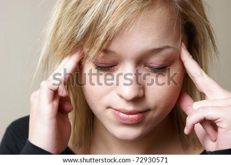 A young woman relieves the pain from her headache by putting pressure on her temples.