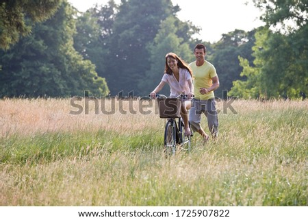 A young woman riding a bicycle through a field with her boyfriend running after her