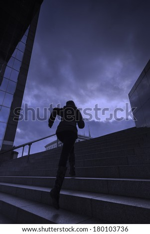 A young woman runs up city steps / woman running up city steps