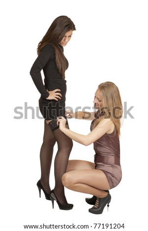 a young woman sat down and adjusts his girlfriend dress isolated on white background