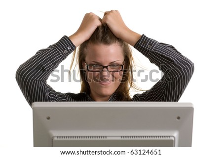 A young woman scrunches her face and pulls her hair as her computer crashes