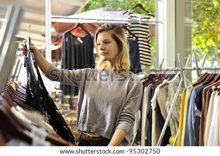 a young woman selects a dress from a well stocked rack in a clothing boutique